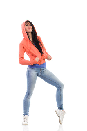 Happy female dancer in a hood posing with hands in pockets. Full length studio shot isolated on white.