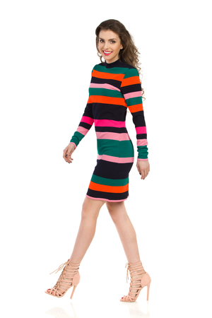 Smiling fashion model in colorful striped mini dress and high heels is walking and looking at camera. Side view. Full length studio shot isolated on white. Stock Photo