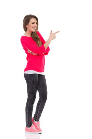 Souriante jeune femme pointant sur un espace vide. Coup de studio de pleine longueur isolé sur blanc. Banque d'images - 80608544