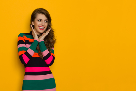 Excited beautiful young woman in colorful vibrant striped dress is holding head in hands, looking away and smiling. Three quarter length studio shot on yellow background.