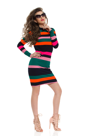 Beautiful young woman in colorful striped mini dress, sunglasses and high heels is posing with hand on hip. Full length studio shot isolated on white.
