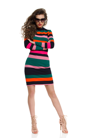 legs apart: Beautiful young woman in colorful striped mini dress, sunglasses and high heels is posing with arms crossed. Full length studio shot isolated on white.