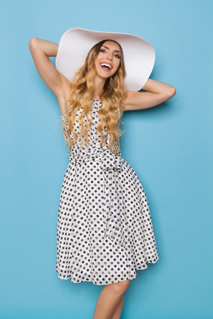 Beautiful young woman in white dotted summer dress and sun hat is holding hands behind head, looking at camera and smiling. Three quarter length studio shot on blue background.