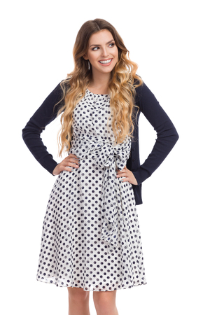Beautiful young woman in white dotted summer dress and blue cardigan is holding hands on hip, looking away and smiling. Three quarter length studio shot isolated on white. Stock Photo