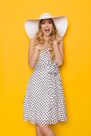 Beautiful young woman in white dotted summer dress and sun hat is holding hands on chest, looking at camera and shouting. Three quarter length studio shot on yellow background.
