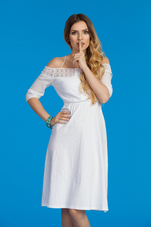 Beautiful young woman in white summer dress is holding finger on lips, sushing and looking at camera. Three quarter length studio shot on blue background. Stock Photo