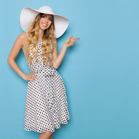 Beautiful young woman in white dotted summer dress and sun hat is pointing, looking at camera and smiling. Three quarter length studio shot on blue background.