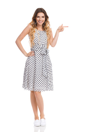 Beautiful young woman in white dotted dress and sneakers is standing, holding hand on hip, pointing, smiling and looking at camera. Front view. Full length studio shot isolated on white. Stock Photo