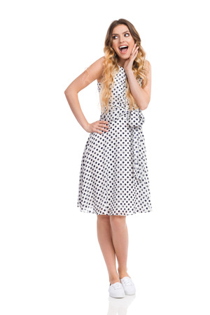 f4ee6321669f  81871477 - Beautiful young woman in white dotted dress and sneakers is  standing