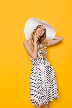 Beautiful young woman in white dotted summer dress and sun hat is smiling, holding hand on chin and looking up at copy space. Three quarter length studio shot on yellow background.