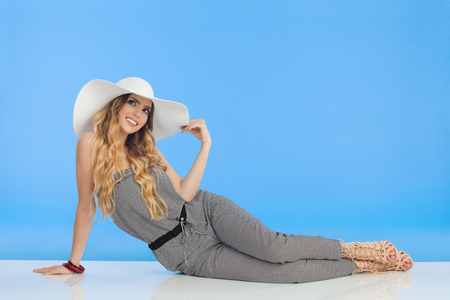 Young fashionable woman in jumpsuit, high heels and white sun hat is sitting relaxed on floor and looking up. Full length studio shot on blue background.