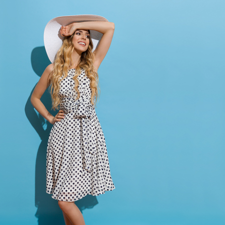 Beautiful young woman in white dotted summer dress and summer hat is standing in sunlight, holding hand on forehead, looking away and smiling. Three quarter length studio shot on blue background.
