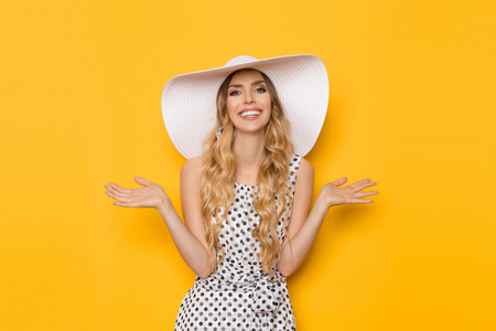 Beautiful young woman in white dotted summer dress and sun hat is holding hand raised, presenting and looking at camera. Three quarter length studio shot on yellow background.