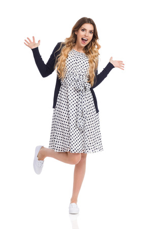 Beautiful young woman in white dotted summer dress and blue cardigan and sneakers is standing on one leg, holding arms outstretched and laughing. Full length studio shot isolated on white. Stock Photo