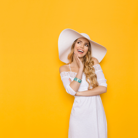 Beautiful young woman in white summer dress and sun hat is smiling, holding hand on chin and looking away at copy space. Three quarter length studio shot on yellow background.