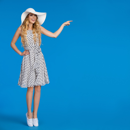 Beautiful young woman in white dotted summer dress, sneakers and sun hat is standing tiptoe, looking at camera, talking and pointing. Full length studio shot on blue background. Stock Photo