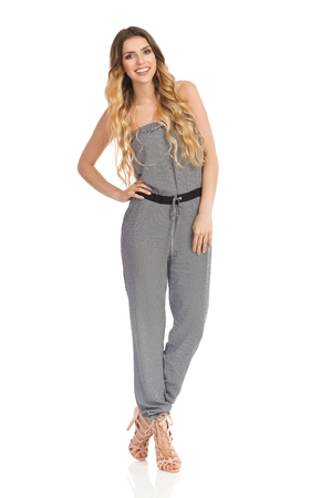 Beautiful young woman in dotted jumpsuit and high heels is standing with hand on hip, looking at camera and smiling. Full length studio shot on isolated on white.