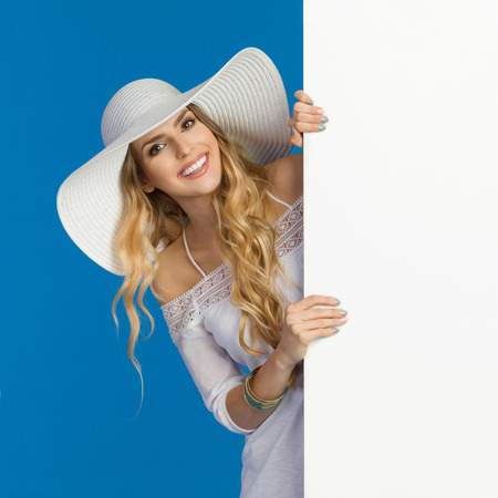 Beautiful young woman in white summer dress and sun hat is standing behind big white banner and smiling. Waist up studio shot on blue background.