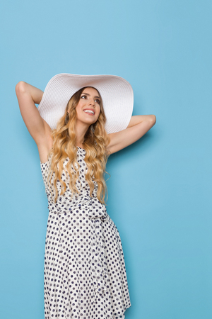 Beautiful young woman in white dotted summer dress and sun hat is holding hands behind head, looking up and smiling. Three quarter length studio shot on blue background.