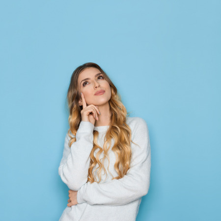 Beautiful young woman in light blue pastel sweater is holding hand on chin, looking up and planning. Waist up studio shot on blue background. 版權商用圖片