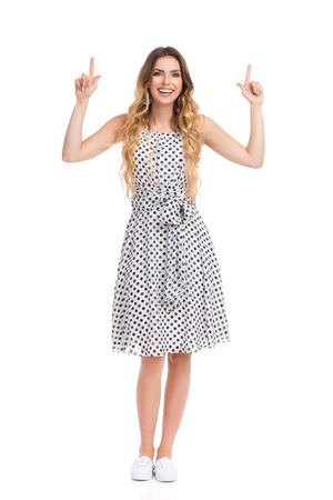 Beautiful young woman in white dotted dress and sneakers is standing, holding arms outstretched, pointing up, smiling and looking at camera. Front view. Full length studio shot isolated on white. Stock Photo