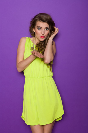 Beautiful young woman in lime green mini dress is sending a kiss. Three quarter length studio shot on violet background.