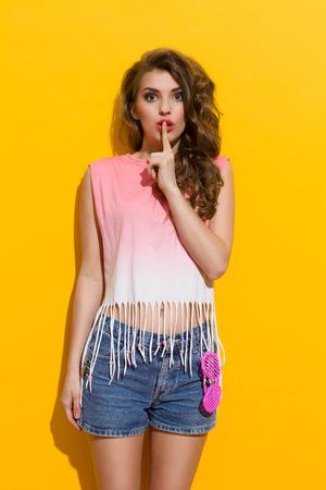 아름 다운 젊은 여자는 입술에 검지 손가락을 잡고있다. 3 분기 길이 스튜디오 노란색 배경에 쐈 어.