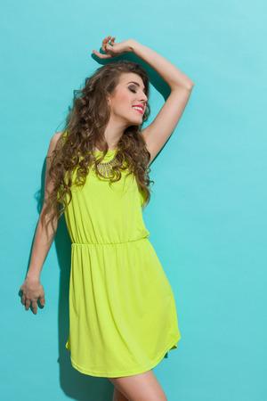 평온한 소녀 라임 녹색 드레스에 포즈입니다. 3 분기 길이 스튜디오 청록색 배경에 쐈 어.