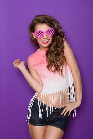 아름 다운 젊은 여자 분홍색 안경에서 포즈입니다. 3 분기 길이 스튜디오 바이올렛 배경에 쐈 어.