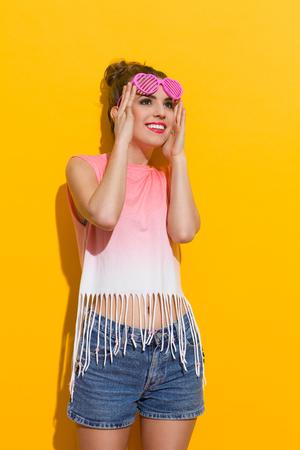 이 마에 핑크 선글라스를 들고 햇빛에 아름 다운 여자를 웃 고. 3 분기 길이 스튜디오 노란색 배경에 쐈 어.