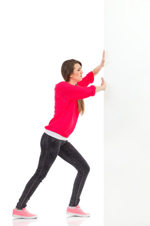 Young woman pushing the wall. Full length studio shot isolated on white.