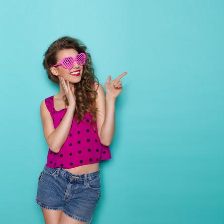 심장 모양의 안경에 젊은 여자를 웃 고 복사본 공간에서 가리키는. 3 분기 길이 스튜디오 청록색 배경에 쐈 어.