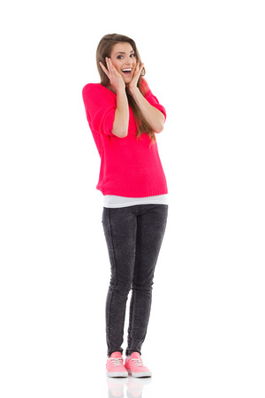 Surprised young woman shouting and holding head. Full length studio shot isolated on white. Stock Photo