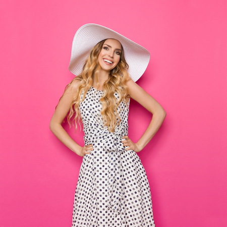simple girl: Beautiful young woman in white dotted summer dress and sun hat is standing with hands on hip, smiling and looking at camera. Three quarter length studio shot on pink background. Stock Photo