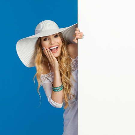 Beautiful young woman in white summer dress and sun hat is standing behind big white banner, holding hand on chin and laughing. Waist up studio shot on blue background.