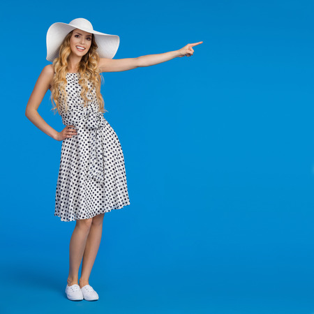 Beautiful young woman in white summer dress, sneakers and sun hat is standing, pointing and looking at camera, Front view. Full length studio shot on blue background.