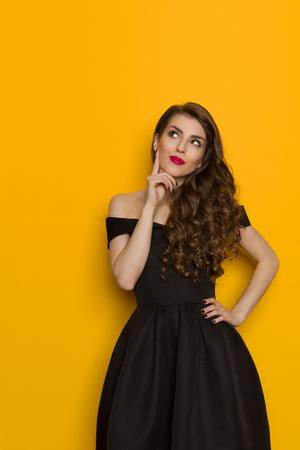 La mujer joven hermosa en vestido de coctel negro elegante está llevando a cabo la mano en la barbilla, pensando y mirando para arriba. Estudio de la longitud de tres cuartos tirado en fondo amarillo. Foto de archivo - 84117241