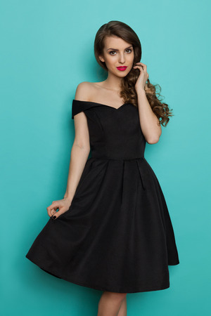 Beautiful young woman in elegant black cocktail dress. Three quarter length studio shot on turquoise background. 스톡 콘텐츠
