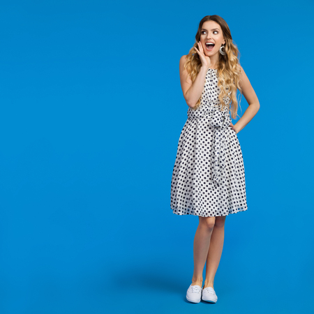 Beautiful young woman in white summer dress and sneakers is holding hand on chin, shouting and looking away. Full length studio shot on blue background.