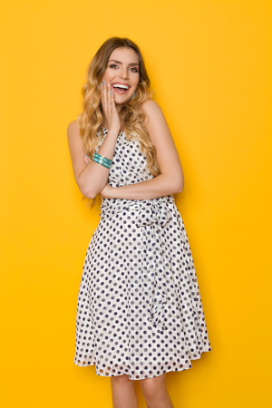 Beautiful young woman in white dotted summer dress is holding hand on chin, looking at camera and laughing. Three quarter length studio shot on yellow background.