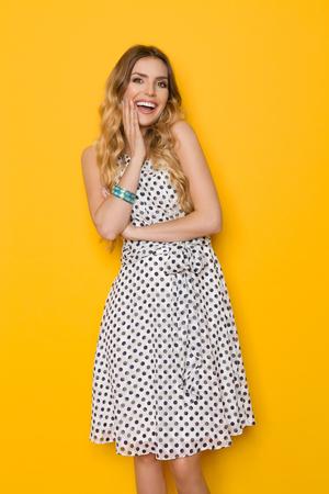 4afcce47ad5e ... im Weiß punktierte Sommerkleid hält Hand auf Kinn und betrachtet Kamera  und das Lachen. Längenatelieraufnahme mit drei Vierteln auf gelbem  Hintergrund.