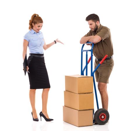 Sad Male Messenger steht mit Stapel von Pakete und überrascht Frau schaut auf ihn und Gestikulieren. In voller Länge Studioaufnahme auf isoliert auf weiß. Standard-Bild - 84481751