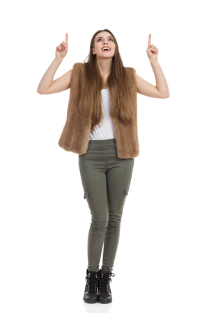 Beautiful young woman in brown fur waistcoat, khaki pants and black boots is holding arms raised, looking up and pointing. Full length studio shot isolated on white. Stock Photo