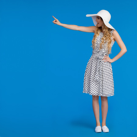 Beautiful young woman in white summer dress, sneakers and sun hat is standing, pointing and looking away, Side view. Full length studio shot on blue background. Stock Photo