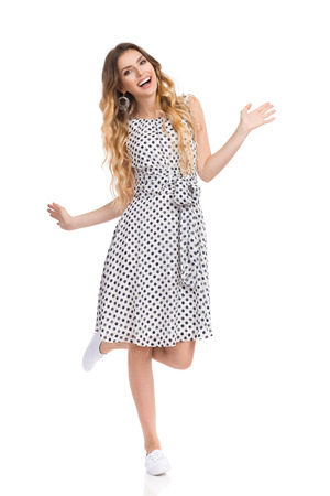 Beautiful young woman in white dotted dress and sneakers is standing on one leg, holding arms outstretched, laughing and looking at camera. Full length studio shot isolated on white.
