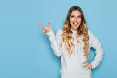Beautiful young woman in pastel blue sweater is holding hand on hip, looking at camera, pointing and laughing. Waist up length studio shot on turquoise background. 写真素材