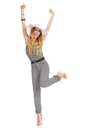 Beautiful young woman in dotted jumpsuit, sun hat and high heels is standing on one leg with arms raised, looking at camera and shouting. Full length studio shot on isolated on white.