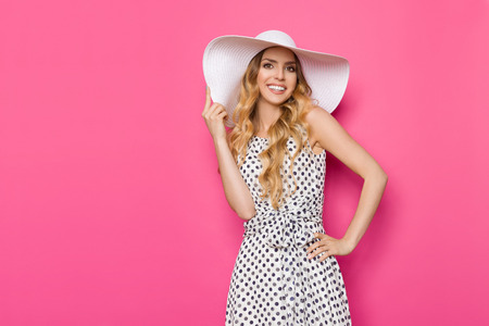 Beautiful young woman in white dotted summer dress and sun hat is standing with hand on hip, smiling and looking at camera. Three quarter length studio shot on pink background. Imagens