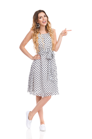Beautiful young woman in white dotted dress and sneakers is standing, pointing right, talking and looking at camera. Front view. Full length studio shot isolated on white.