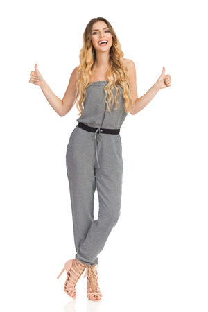 Beautiful young woman in dotted jumpsuit and high heels is standing, showing thumbs up, looking at camera and smiling. Full length studio shot on isolated on white.